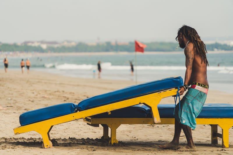 Hombre colocándo hamacas en la playa
